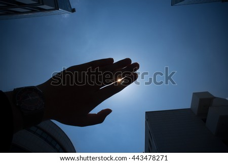 Silhouette of a hand under strong, drought making sunlight.