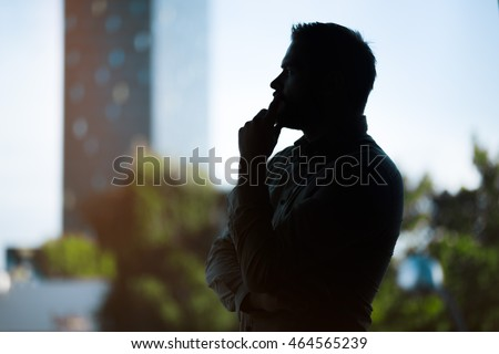 silhouette of a handsome young businessman thinking in front of a skyscraper, graded with a lens flare