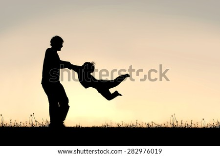 Silhouette of a happy father holding his little child's arms and spinning him in circles on a summer day.