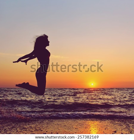 silhouette of a happy woman jumping on a sunset on the sea. healthy lifestyle. freedom, inspiration and breakthrough. colorized and toned photo - stock photo