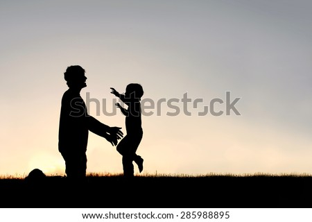 Silhouette of a happy young child smiling as he runs to greet his father with a hug at sunset on a summer day. - stock photo