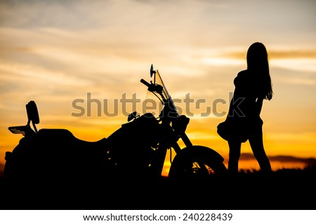 Silhouette of a happy young woman in short skirt posing by a motorcycle on sunset in summer outdoors on sky background - stock photo