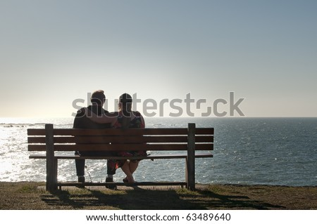 Silhouette of a heterosexual couple enjoying the afternoon on a calm and peaceful relaxing in front of the ocean view. Copyspace above with room for text. - stock photo