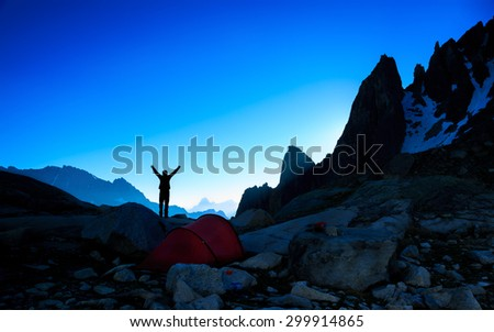 Silhouette of a hiker enjoying a new dawn in the mountains. Sports en outdoor concept. - stock photo