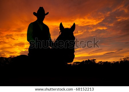 Silhouette of a horse and a rider in a cowboy hat against late evening storm clouds - stock photo
