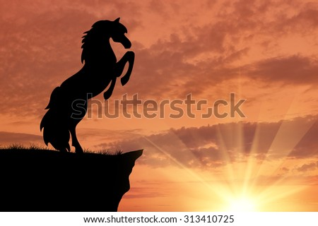 Silhouette of a horse at the edge of the mountains at sunset - stock photo