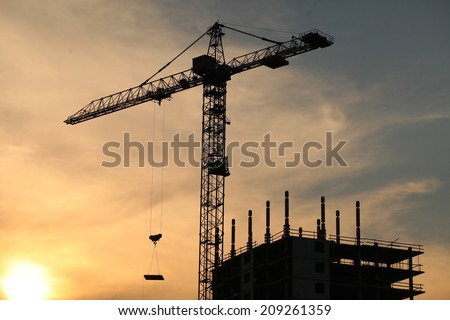 silhouette of a house under construction with a crane on the sunset background.horizontal frame