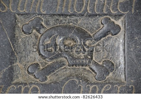 silhouette of a human skull and bones on a black grave stone - stock photo