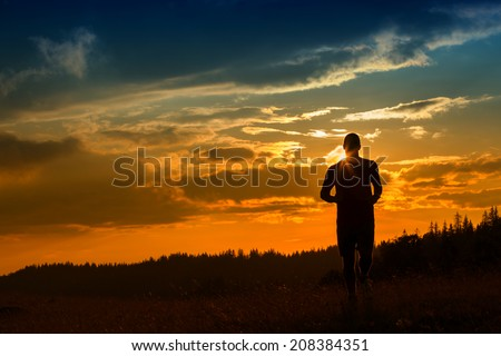silhouette of a jogger in beautiful sunrise - stock photo