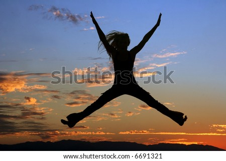 Silhouette of a jumping woman at sunset