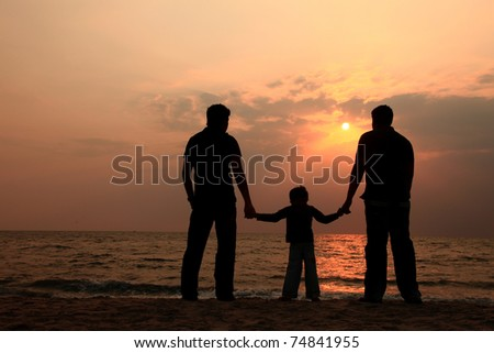 Silhouette of a kid and two adults watching sunset in a beach - stock photo