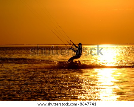 Silhouette of a kitesurf on a gulf on a sunset 2 - stock photo