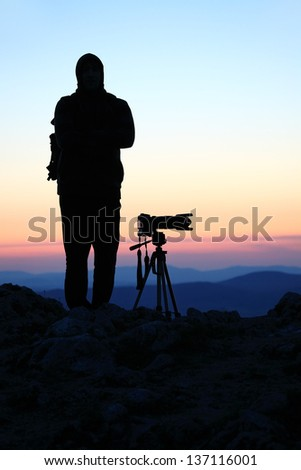 Silhouette of a landscape photographer in twilight - stock photo