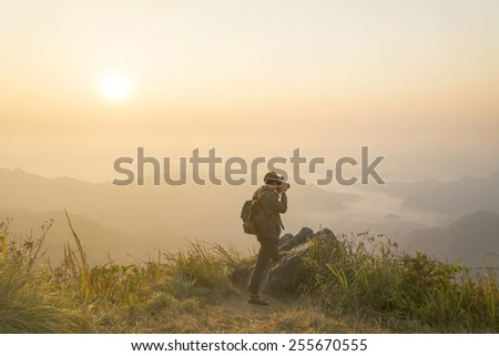 Silhouette of a landscape photographer with sunrise on mountain. - stock photo