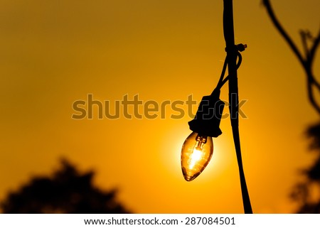 Silhouette of a light bulb at sunset, energy concept.
