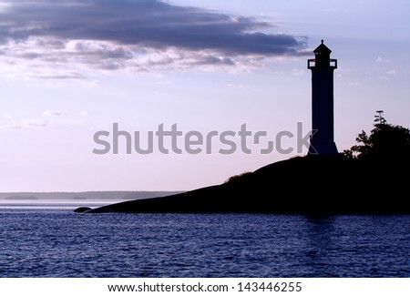 Silhouette of a  lighthouse at the sunrise.