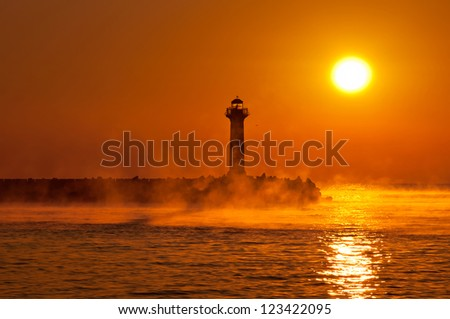 silhouette of a lighthouse in a foggy morning at sunrise - stock photo