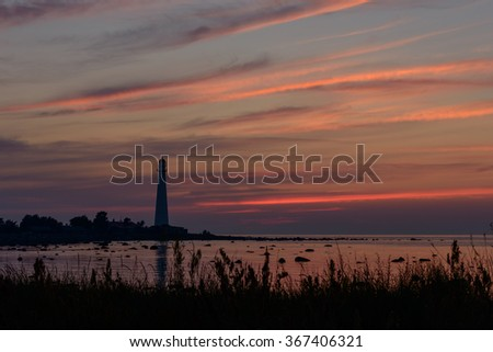 Silhouette of a lighthouse with sunset sky.