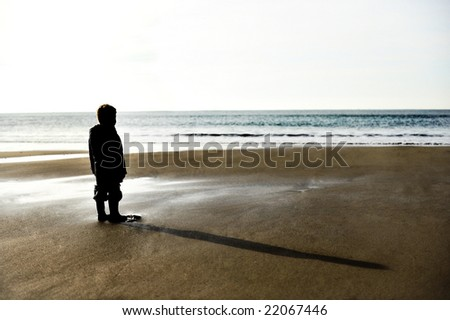silhouette of a little boy on a beach - stock photo