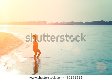 Silhouette of a little boy standing in the water near the shore in the sunlight, at sunset or sunrise