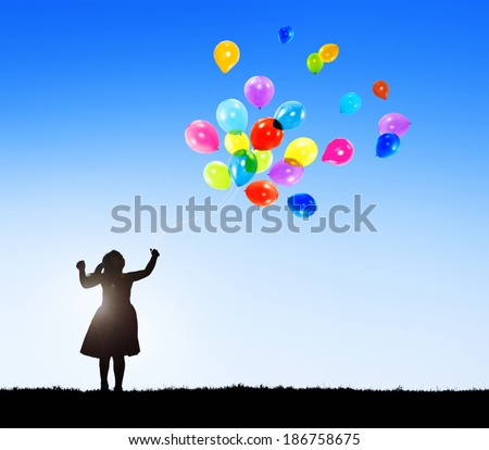 Silhouette of a Little Girl with Balloons and Copy Space - stock photo