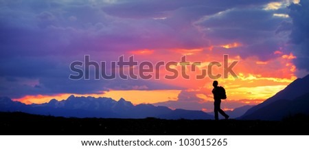 Silhouette of a lonely hiker in the mountains at sunset - stock photo