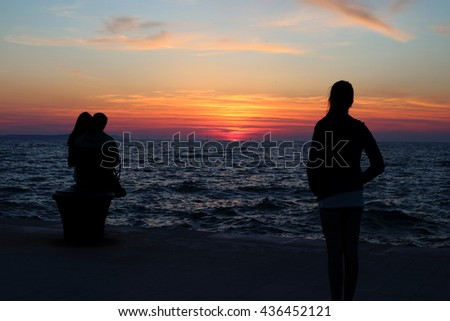 Silhouette of a lonely womanl looking at a her boyfriend cheating on her with another woman upon sunset at the seaside, their relationship is sinking like the setting sun - stock photo