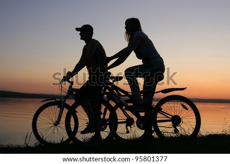 silhouette of a loving couple at sunset - stock photo