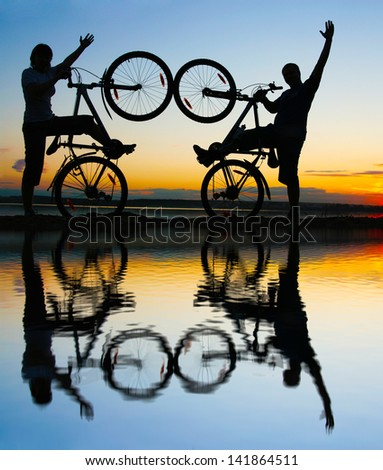 silhouette of a loving couple at sunset  with reflection on water - stock photo