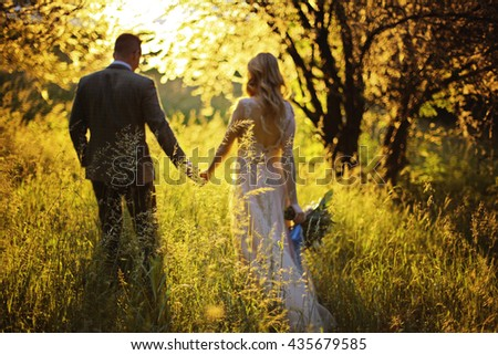 Silhouette of a loving couple on the background of the setting sun, hills, meadow and trees. Just married. Walk at sunset through the mountains at sunset.Romantic Married young family - stock photo
