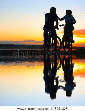 silhouette of a loving couple with reflection on water copy Space for inscription - stock photo