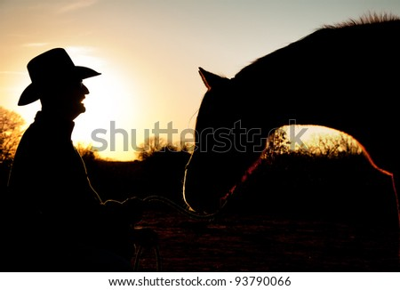Silhouette of a man and his horse against sunset sky, with horse reaching towards man - stock photo