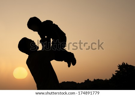 Silhouette of a man and his son with sunset background - stock photo