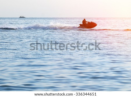 Silhouette of a man and young girl in motion on jetski on the sea - stock photo