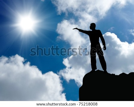 silhouette of a man at the top of the mountain against the sky