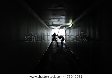 Silhouette of a man beating up a woman with wooden stick in a dark tunnel. Violence against women concept. Real people, copy space