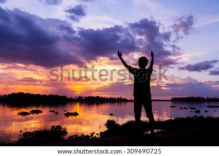 Silhouette of a man beside the river at sunset - stock photo