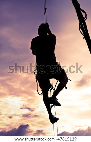 Silhouette of a Man Climbing to the Top - stock photo