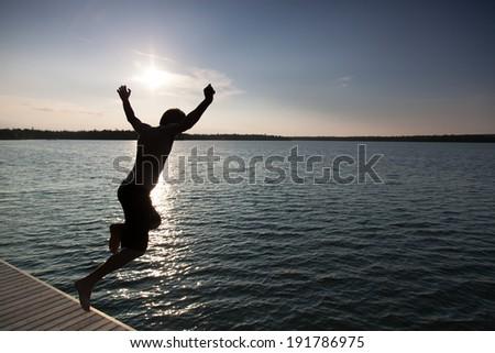 Silhouette of a man diving in a bay, Georgian Bay, Tobermory, Ontario, Canada - stock photo
