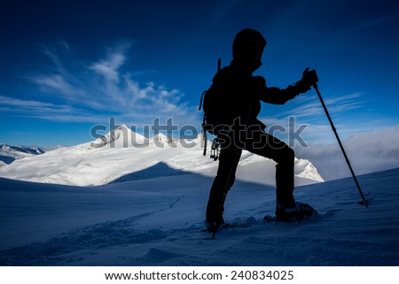 Silhouette of a man doing a snowshoe mountain ascend - stock photo