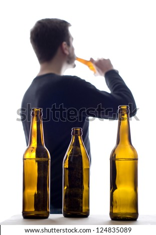 Silhouette of a man drinking beer. In front beer bottles in focus. Man out of focus. Strong contrast. Isolated on  a white background. Have a look also at my other images of the same series. - stock photo
