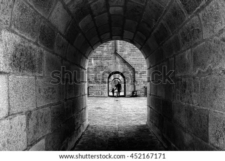 Silhouette of a man/father/parent and a child walking through the archs of the old bridge in Morlaix, Finistere, Brittany, France / Black and white photo of passage with archs of old stone bridge - stock photo