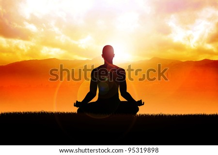 Silhouette of a man figure meditating in the outdoors - stock photo