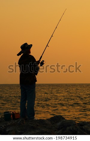 Silhouette of a man fishing - stock photo