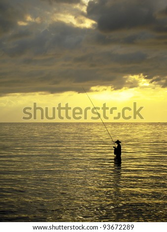 Silhouette of a man fishing in a sunset, Bali, Indonesia - stock photo