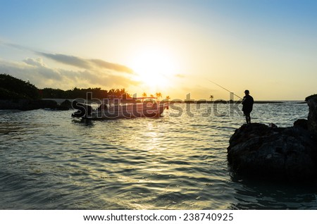 Silhouette of a man fishing in the caribbean sea on a beautiful sunrise. Fisherman enjoying tranquility and leisure in a beautiful natural scene. - stock photo