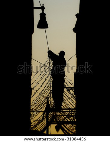 Silhouette of a man fixing street decorations - stock photo