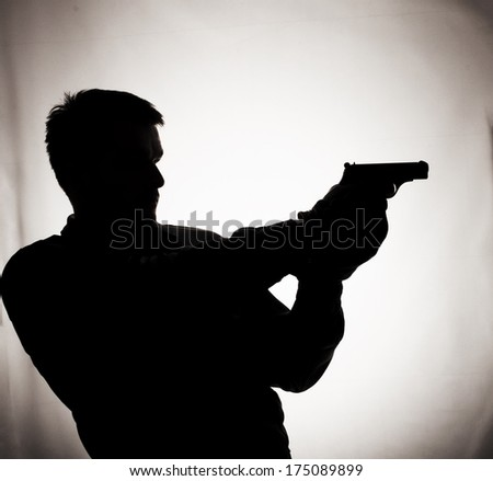 Silhouette of a man holding a gun - stock photo