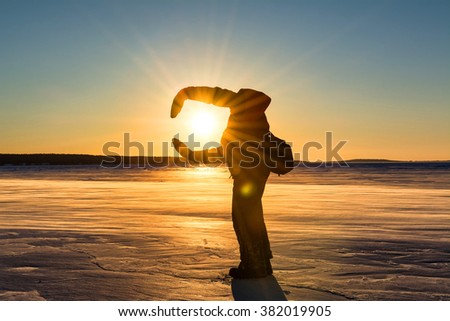 Silhouette of a man hugging the sun on a windswept and desolate section of snowy ice on Lake Superior. - stock photo
