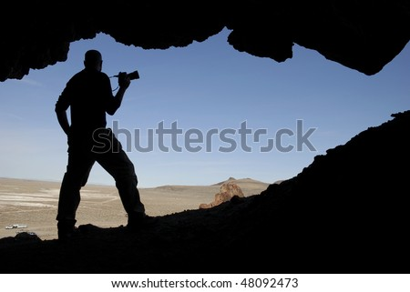 Silhouette of a man in a cave with a camera in his hand, looking out at a Nevada landscape.